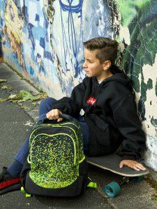 Junge sitzt auf seinem Skateboard und hat vor sich den neoxx Fly Schulrucksack im Design Pixel in my mind stehen.