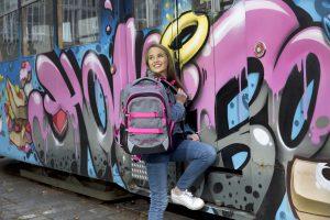 Mädchen steht mit Ihrem coolen neoxx Active Schulrucksack im Design Pink and Famous vor einem Zug, der mit Graffiti besprüht ist.